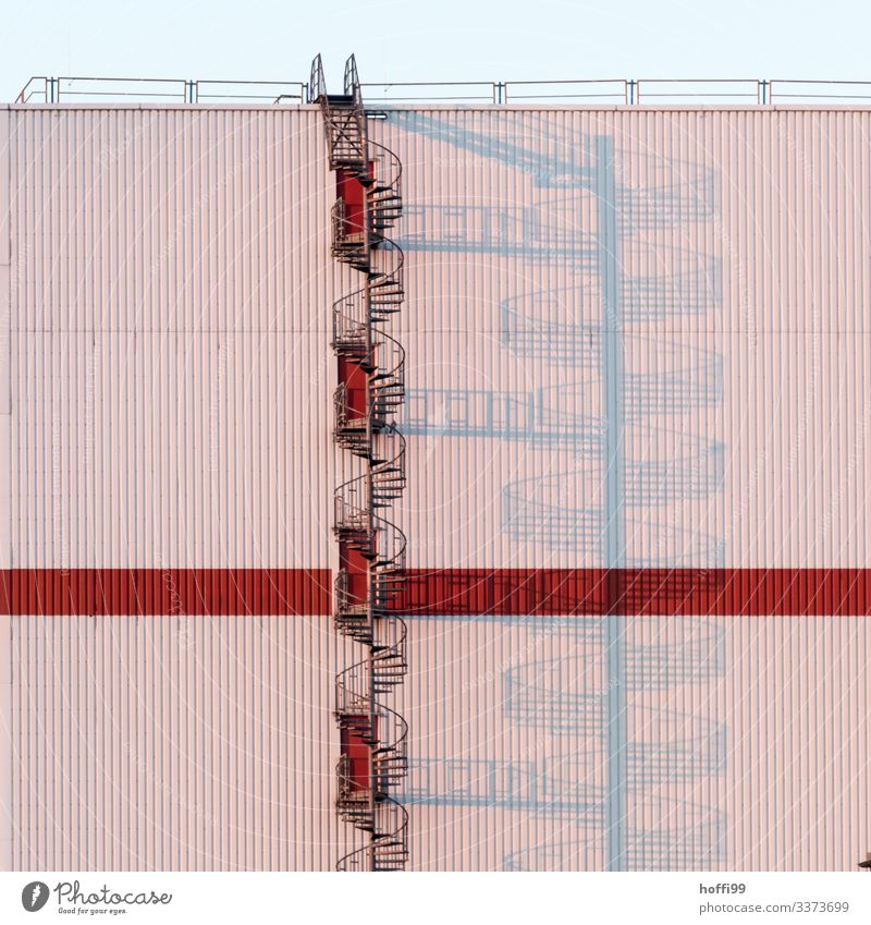Wendeltreppe im Sonnenaufgang mit langen Schatten Architektur Lager Treppe Fassade Industrieanlage Symmetrie Außenaufnahme rot modern ästhetisch Morgen