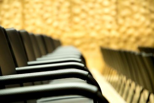 Sitzreihe im Theater mit Fokus auf einer Armlehne Gebäude ästhetisch elegant nah modern Klischee Wärme gold schwarz Erwartung Freude geheimnisvoll Inspiration