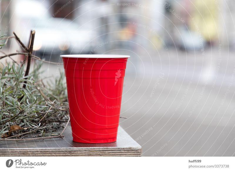 roter Plastikbecher mit Rosmarin auf einem Tisch Rot roter Becher Müll Plastikmüll Umweltbelastung Freisteller selektiver fokus