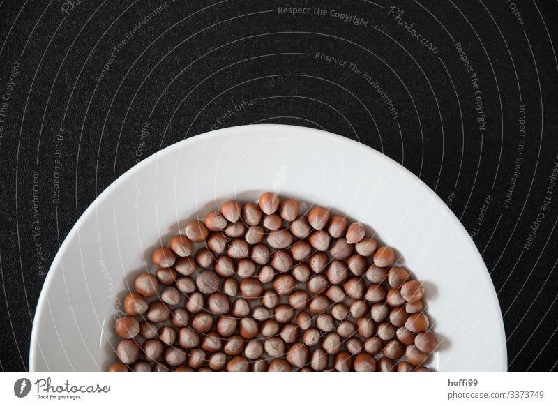 Haselnüsse in halbrunder Schale mit schwarzem Hintergrund viele Haselnüsse viele Nüsse Rundes Muster angeordnet Detail der Haselnuss Detailaufnahme sortiert