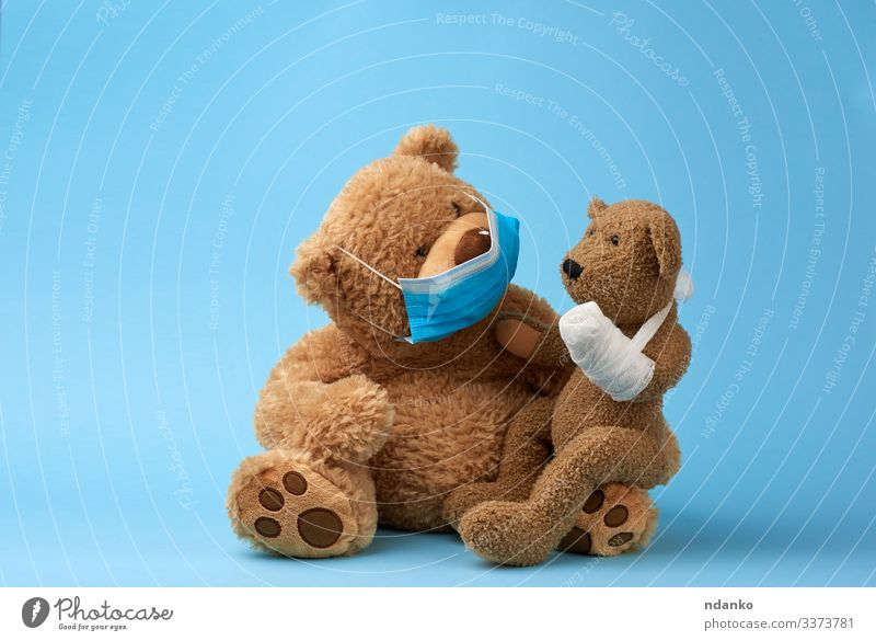 großer brauner Teddybär sitzt in einer medizinischen Maske Freude Krankheit Medikament Krankenhaus Baby Kindheit Tier Pfote Spielzeug Puppe Traurigkeit klein