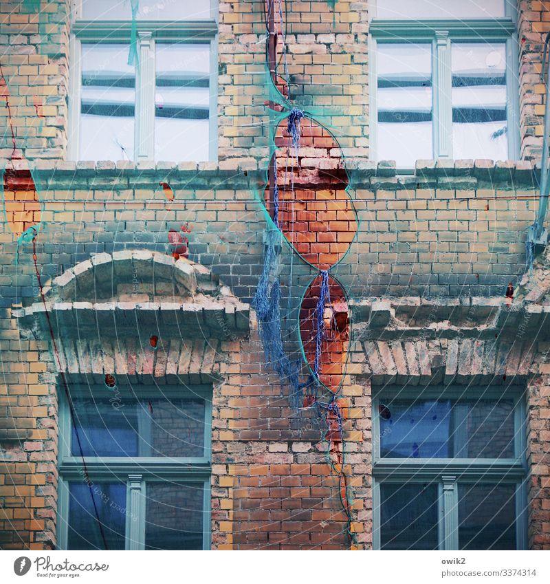 Ewige Baustelle Stadt Haus Mauer Wand Fassade Fenster Bauplane Loch Schaden Stein Glas Kunststoff alt trashig trist Verfall Vergangenheit Vergänglichkeit