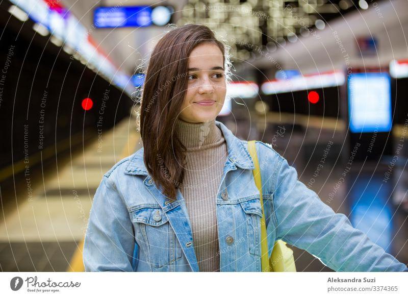Teenager-Mädchen in Jeans mit Rucksack steht in der U-Bahn-Station, hält Smartphone in der Hand, scrollt und schreibt SMS, lächelt und lacht. Futuristisch helle U-Bahn-Station. Finnland, Espoo