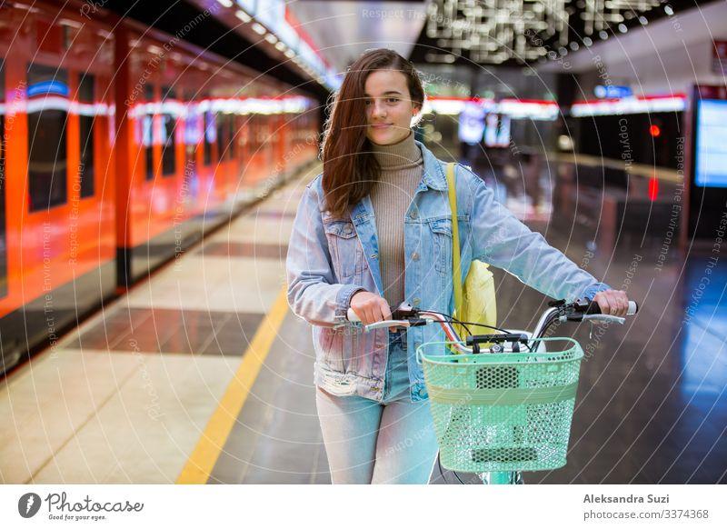 Jugendliche mit Rucksack und Fahrrad in der U-Bahn-Station Aktion Fahrradfahren lässig Freizeitbekleidung Freundlichkeit heiter Großstadt Ausflugsziel