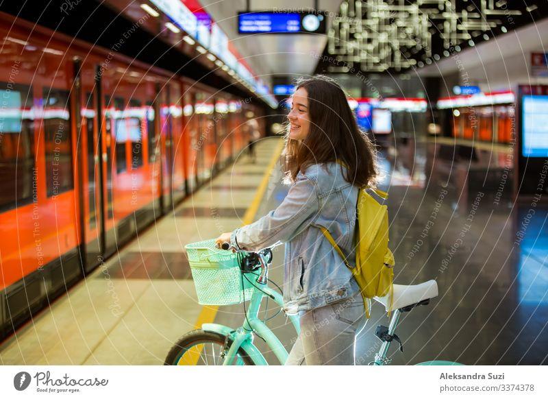Teenager mit Rucksack und Fahrrad auf der U-Bahn-Station stehend, Smartphone in der Hand haltend, blätternd und simsend, lächelnd und lachend. Futuristisch helle U-Bahn-Station. Finnland, Espoo