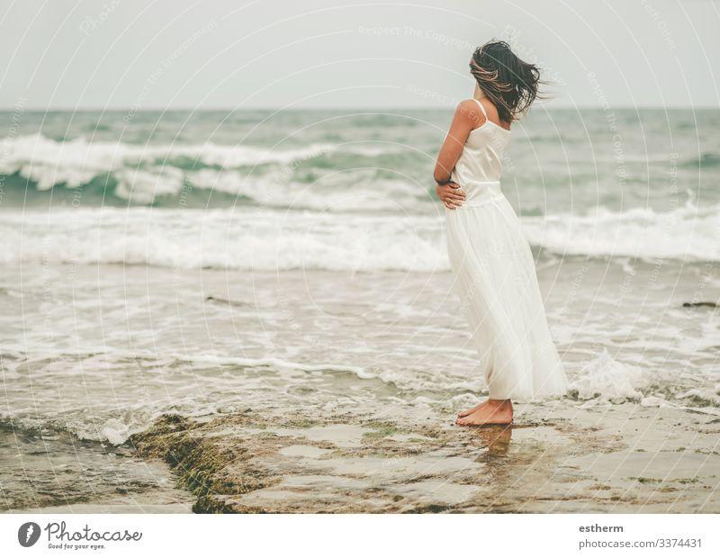 Rückenansicht einer nachdenklichen jungen Frau am Strand Junge Frau schön elegant Eleganz träumen träumend Träume Kleid Mode Freiheit Spaß Glamour
