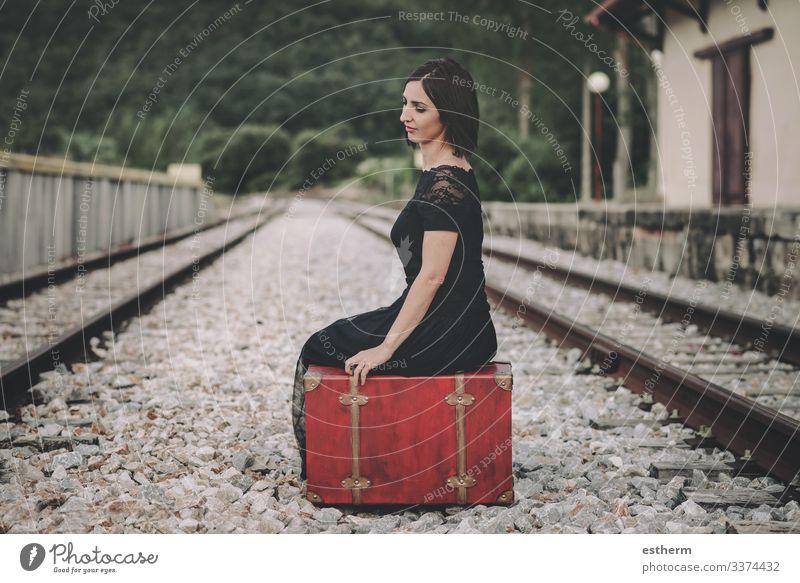 junge Frau, die auf einem Koffer auf dem Bahnhof sitzt Junge Frau schön elegant Eleganz romantisch Zerbrechlichkeit Liebe Weiblichkeit Kleid Nostalgie Freiheit
