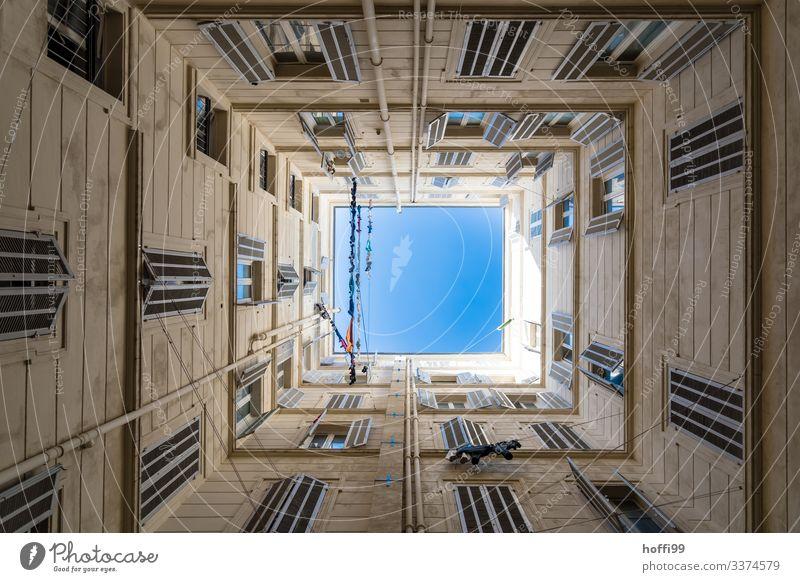 Blick nach oben in einem quadratischen Innenhof mit Wäscheleinen und tiefblauem Himmel Schönes Wetter Haus Mauer Wand Fassade Fenster Fensterladen