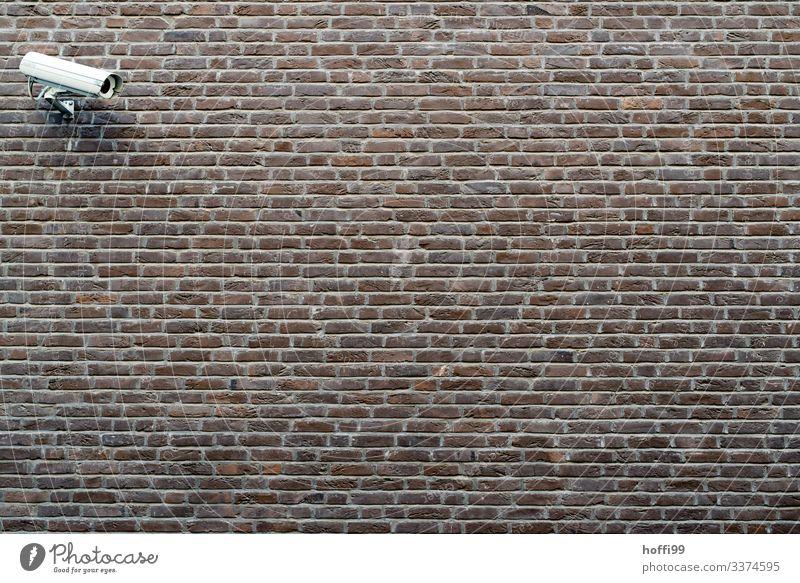 Überwachungskamera an Aussenmauer Gebäude Mauer Wand Fotokamera Backstein Linie Streifen bedrohlich dunkel Stadt Sicherheit Schutz Wachsamkeit Angst