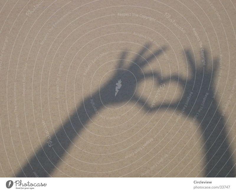 Herzschatten am Strand Glück Sommer Sonne Mensch Hand Sand Liebe Gefühle Schattenspiel Frauenhand herzlich Feiertag spiel mit licht Licht