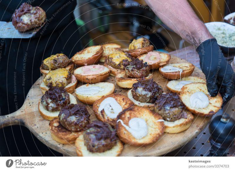 Küchenchef macht Rindfleisch-Burger im Freien auf einem Lebensmittelfestival. Fleisch Brötchen Mittagessen Teller Schreibtisch Restaurant Straße Handschuhe