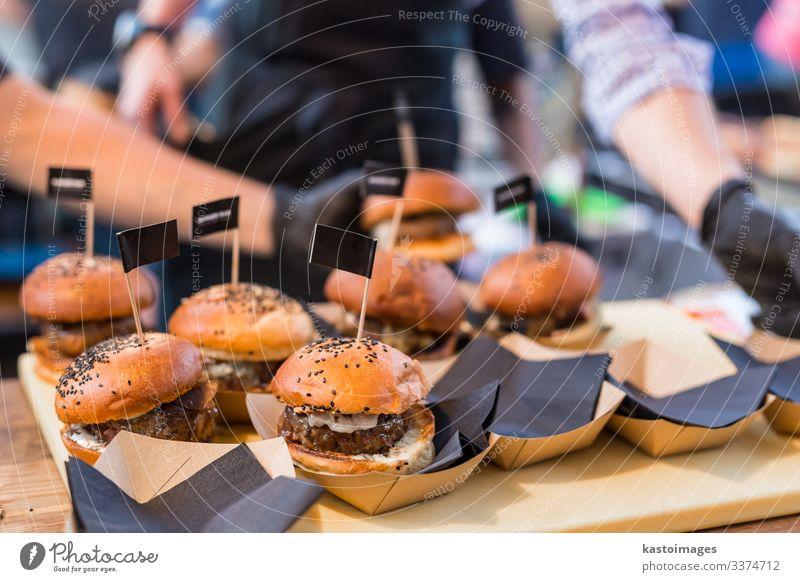 Chefkoch macht Rindfleisch-Burger auf einer Veranstaltung des Lebensmittelfestivals. Fleisch Brötchen Mittagessen Teller Schreibtisch Küche Restaurant Straße