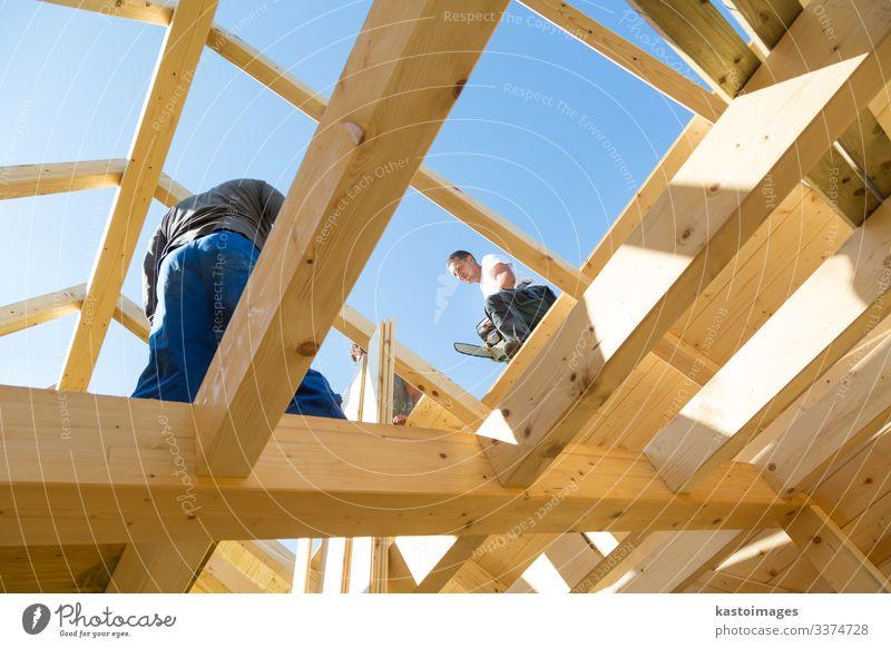 Bauarbeiter bei der Arbeit mit hölzerner Dachkonstruktion. Haus Rahmen heimwärts Bauherr Konstruktion Zimmerer Holz Dachdecker Arbeiter Gebäude Entwicklung
