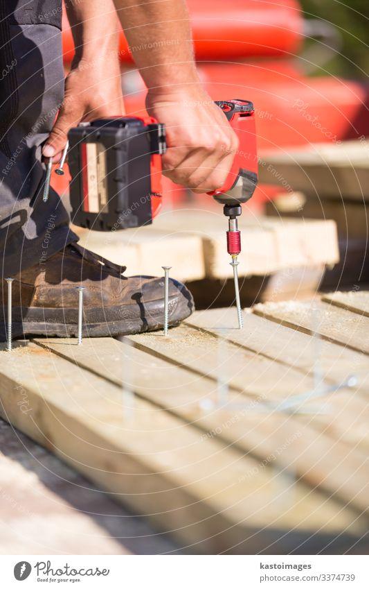 Zimmermann, der mit einem elektrischen Schraubendreher arbeitet. Arbeit & Erwerbstätigkeit Beruf Industrie Werkzeug Mann Erwachsene Hand Accessoire bauen neu