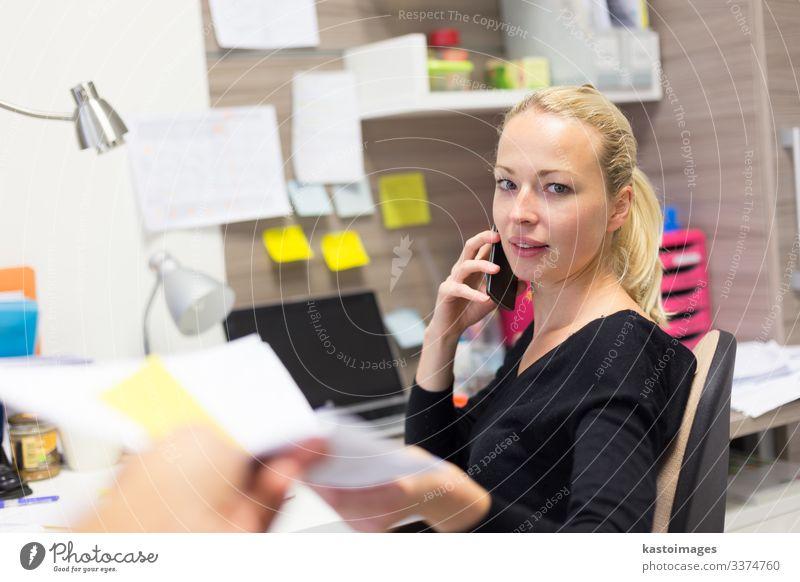 Geschäftsfrau, die mit dem Handy telefoniert und Papiere entgegennimmt. Glück Schreibtisch Tisch Arbeit & Erwerbstätigkeit Beruf Büroarbeit Arbeitsplatz