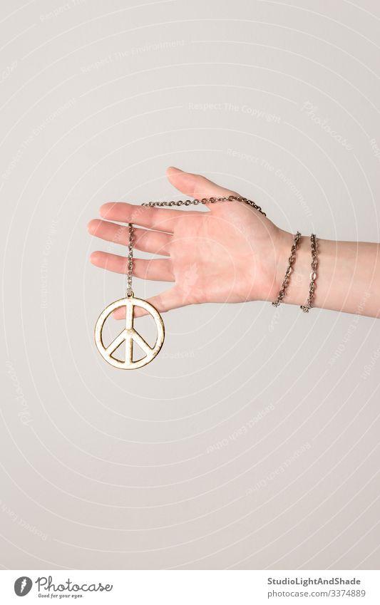 Weibliche Hand hält Friedenszeichen pazifik Arme Finger Frau Mädchen jung Halt Beteiligung Hippie Jugend gold golden grau rosa weiß anketten Armband Schmuck