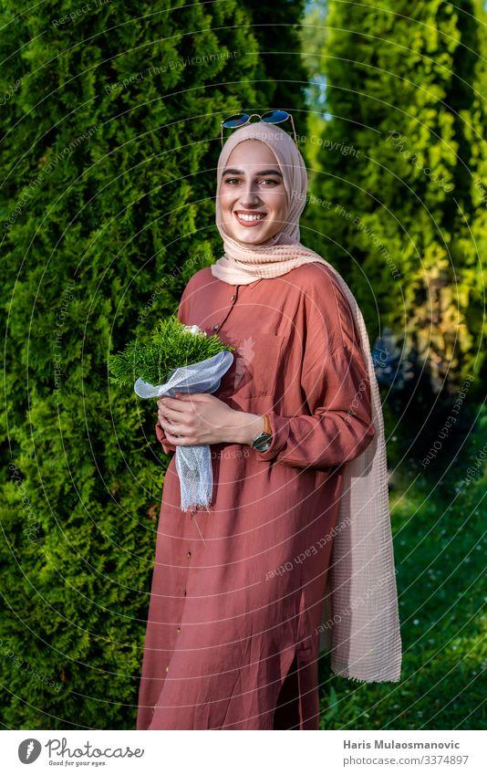 Muslimische Frau im Hidschab mit Blumenstrauß lächelt muslimisch Religion Lächeln Porträt schön beige hell heiter abschließen Bekleidung selbstbewusst Kleid