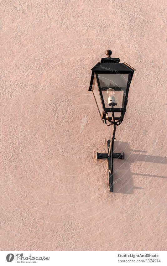 Straßenlampe auf einer strukturierten rosa Wand Straßenlaterne Licht Lampe Laterne Elektrizität gemalt Stein Hintergrund Textur Oberfläche staubig-rosa Pastell