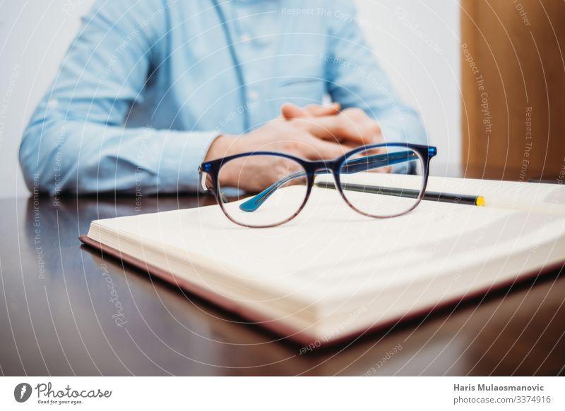 Männerhände, die am Schreibtisch sitzen, mit Buch und Brille studieren und im Büro arbeiten Tisch Bildung Schüler lernen Arbeit & Erwerbstätigkeit Beruf