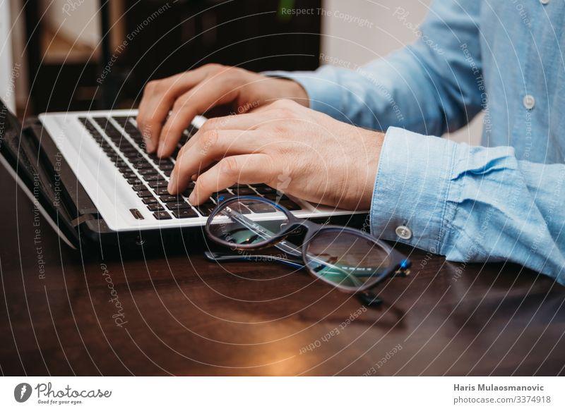 Mann tippt mit der Brille auf dem Schreibtisch mit den Händen am Laptop Notebook Keyboard Technik & Technologie Fortschritt Zukunft Erwachsene Hand Finger 1