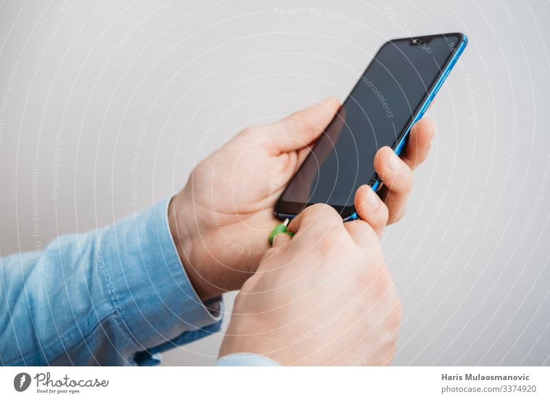 Männerhände halten Smartphone mit Kopfhöreranschluss Telefon Technik & Technologie Unterhaltungselektronik Telekommunikation Internet Hand Coolness blau weiß