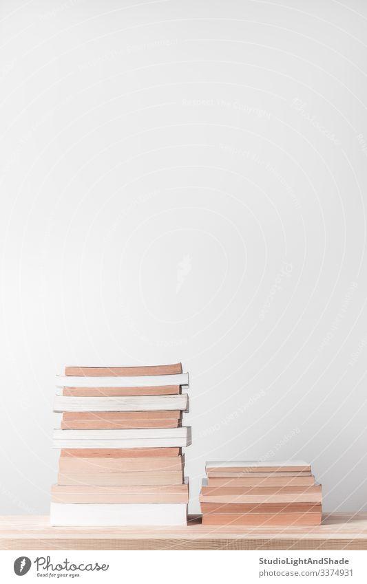 Bücherstapel auf einem Holzregal Buch Wissen Haufen Stapel gestapelt lernen Seiten weiß beige grau Lernen lesen Bücherregal Regal hölzern Tisch Bildung