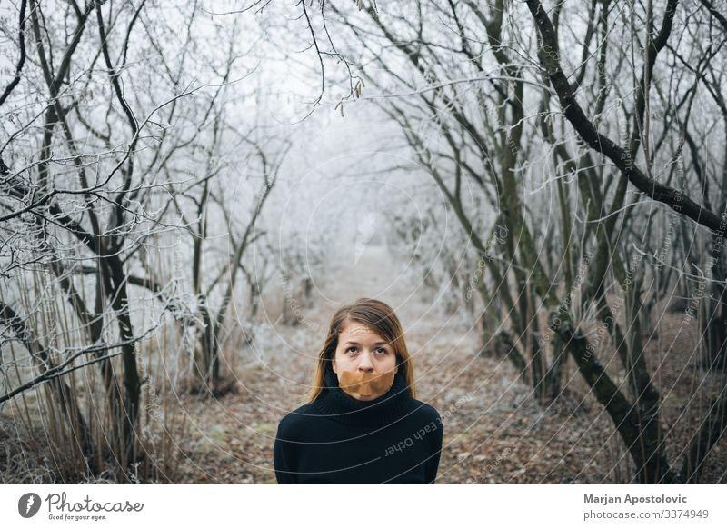 Frau mit Klebeband am Mund im kalten Winterwald Erwachsener Angst Verhalten blond Kaukasier Zensur zivil Konzepte Depression Verzweiflung verzweifelt emotional