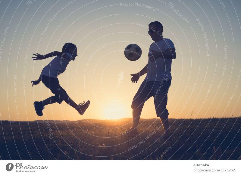 Vater und kleiner Junge spielen auf dem Feld mit einem Fussball. Begriff des Sports. Lifestyle Freude Glück Leben Freizeit & Hobby Spielen Sommer Fußball Kind