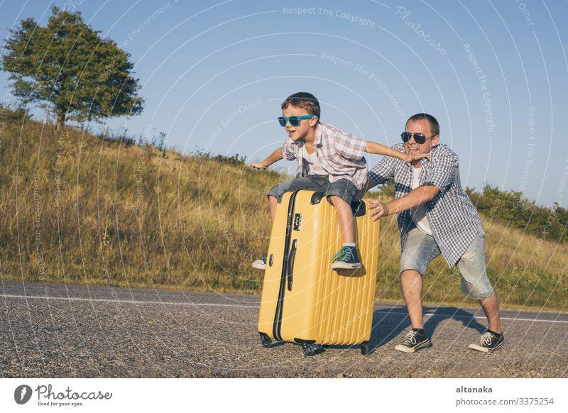 Vater und Sohn spielen zur Tageszeit auf der Straße. Die Menschen haben Spaß im Freien. Konzept eines glücklichen Urlaubs und einer freundlichen Familie.