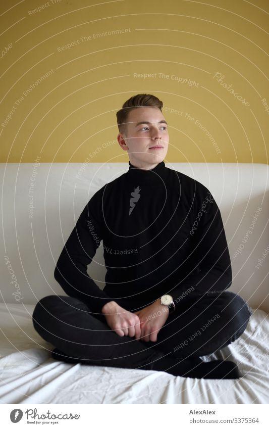 Junger Mann sitzt in Schneidersitz auf Bett vor gelber Wand Lifestyle Stil Freude schön Wohlgefühl Raum Schlafzimmer Jugendliche 18-30 Jahre Erwachsene