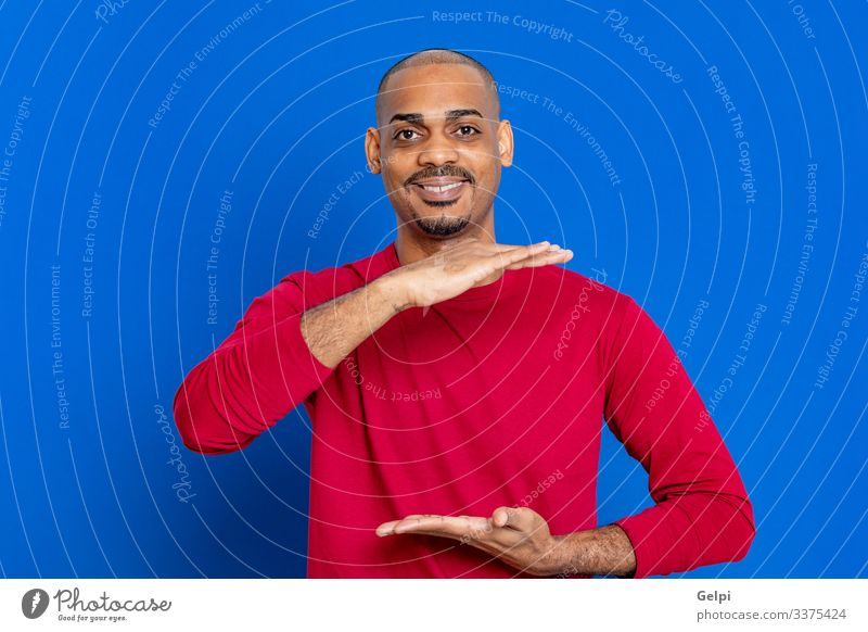 Afrikanischer Mann mit rotem T-Shirt Haare & Frisuren Mensch Erwachsene Hand Finger Afro-Look blau schwarz weiß Farbe Typ Punkt zeigen hindeutend Inserat