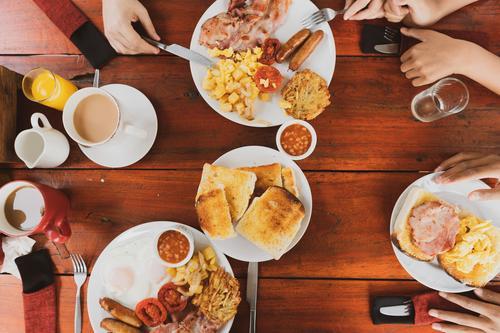 Junge glückliche Familie beim Frühstück Frucht Brot Croissant Marmelade Essen Getränk Saft Kaffee Teller Lifestyle Ferien & Urlaub & Reisen Tisch Küche Stein