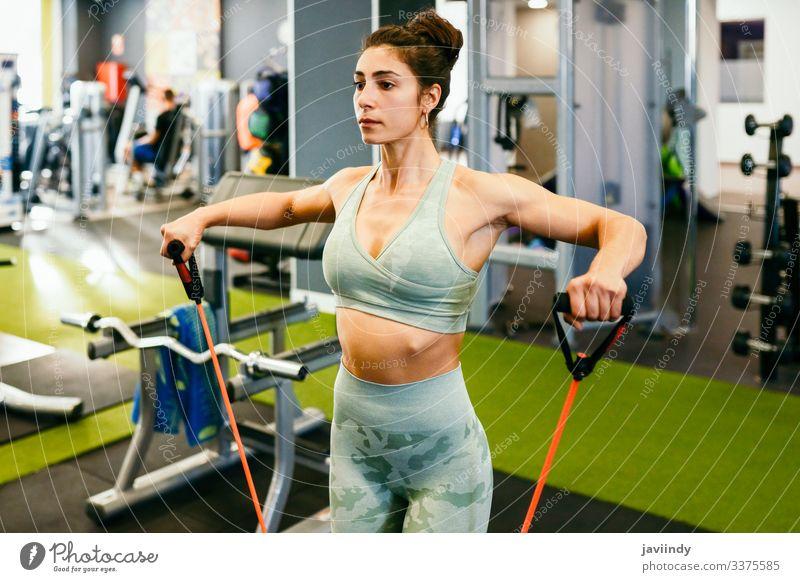 Junge Sportlerin beim Aufwärmen mit Fitnessgummis im Fitnessstudio Frau Training Zahnfleisch elastisch Band Gerät Gesundheit Körper Bizeps Übung Unterleib