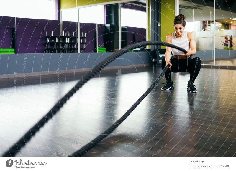 Junge und sportliche Frau, die Trainingsseile in einer Turnhalle benutzt. Seil Fitness Fitnessstudio Sportlerin Athlet aktiv jung muskulös Übung Erwachsener