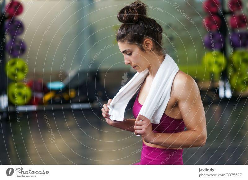 Frau ruht sich nach den Übungen in der Turnhalle aus Handtuch ruhen Pause Mädchen aussruhen jung Sitzen aktiv Fitnessstudio Sport passen Gesundheit Lifestyle