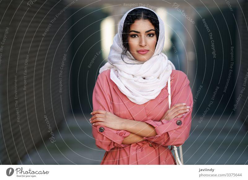 Junge muslimische Frau mit Hijab-Kopftuch beim Spaziergang durch die Innenstadt. arabisch jung Schal Tourist attraktiv schön urban Großstadt Lifestyle Straße
