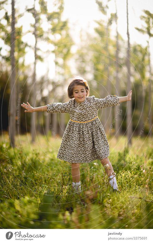 Kleines Mädchen im Naturfeld mit schönem Kleid wenig Kind Glück Kinder Frühling außerhalb Sommer Wiese Spielen Porträt im Freien Mode Fröhlichkeit Baby Blumen