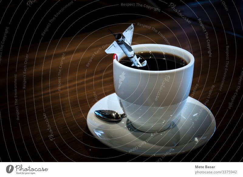 Eine Rakete fiel in eine Tasse Kaffee in einer weißen Tasse. Kaffeetrinken Getränk Heißgetränk Teller Becher Löffel Kaffeemaschine Tisch Beruf