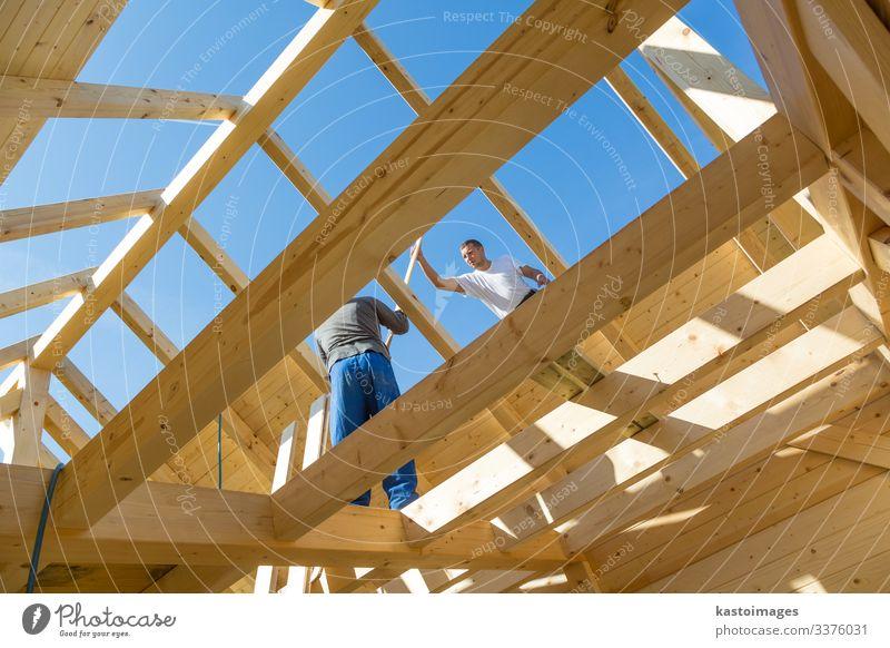 Dachdecker, die vorgefertigte Holzdachkonstruktionen montieren. Konzept der Bauindustrie. Haus Arbeit & Erwerbstätigkeit Handwerker Baustelle Industrie Werkzeug