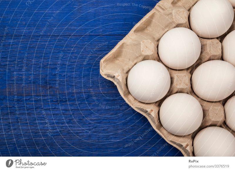 Frische Eier in einem Pappkartentablett auf blauem Hintergrund. Lebensmittel Ernährung Essen Frühstück Lifestyle Design Gesundheit Gesunde Ernährung Fitness