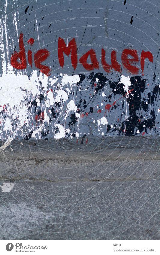 die Mauer steht rot auf der Betonwand in Blau mit Farbklecksen vor einer Straße, geschrieben. Menschenleer Strukturen & Formen Muster Schilder & Markierungen