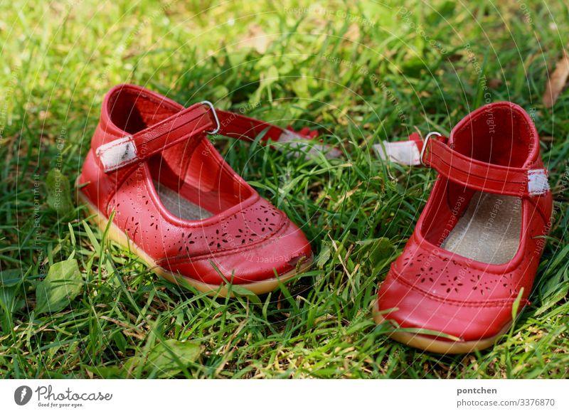 Rote Kinderschuhe im Gras Schuhe ballerinas rot sommerschuhe geöffnet klettverschluss ausziehen gras grün komplementärfarben barfuß wiese freude Rasen
