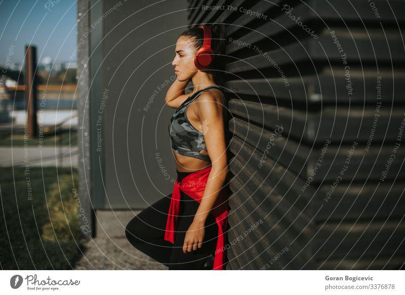 Hübsche junge Frau macht eine Pause nach einem Lauf im Stadtgebiet Lifestyle Erholung Joggen Headset Mensch Junge Frau Jugendliche Erwachsene 1 18-30 Jahre