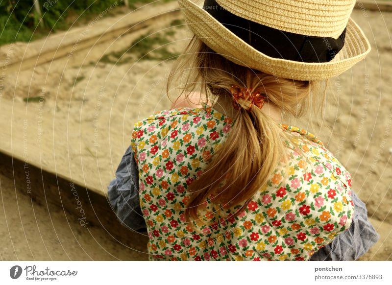 Weibliches Kleinkind von hinten spielt am Sandkasten mädchen kleinkind spielen lange haare zopf blond haargummi hipster blumenmuster kleidung weste Gras