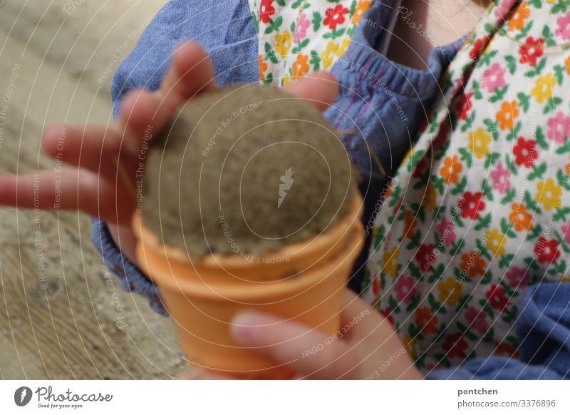 Kinderhände formen eine Eiskugel aus Sand Kleinkind sand spielen freude sandkasten spielplatz muster eis eiswaffel sandförmchen Sommer Farbfoto Außenaufnahme