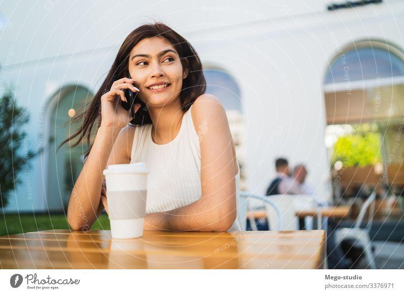 Junge Lateinamerikanerin am Telefon. Glück sprechend Mobile Frau Mädchen im Freien Anruf klug Zelle hübsch jung Kaffeehaus Smartphone Funktelefon Gespräch urban