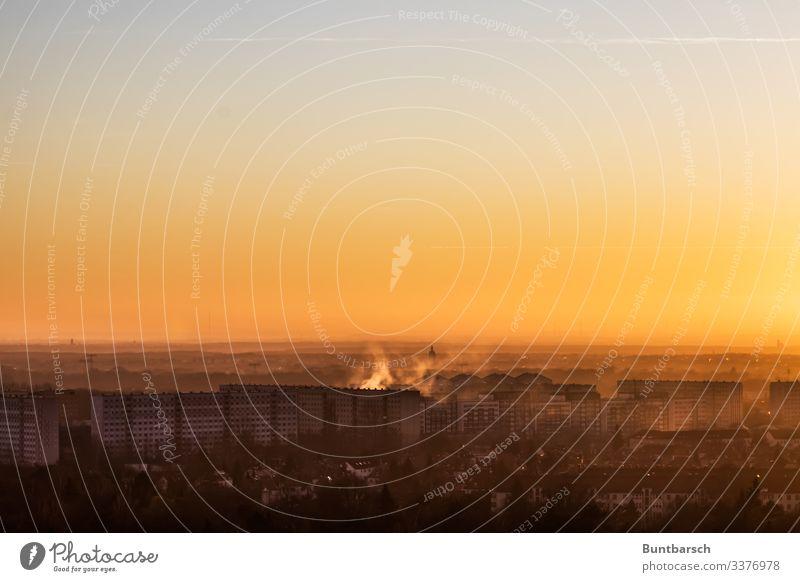 Blick über eine Plattenbausiedlung im Licht eines Sonnenuntergangs Plattenbauten Häuser Mietshäuser Leipzig orange Rauch Nebel Neubausiedlung Himmel