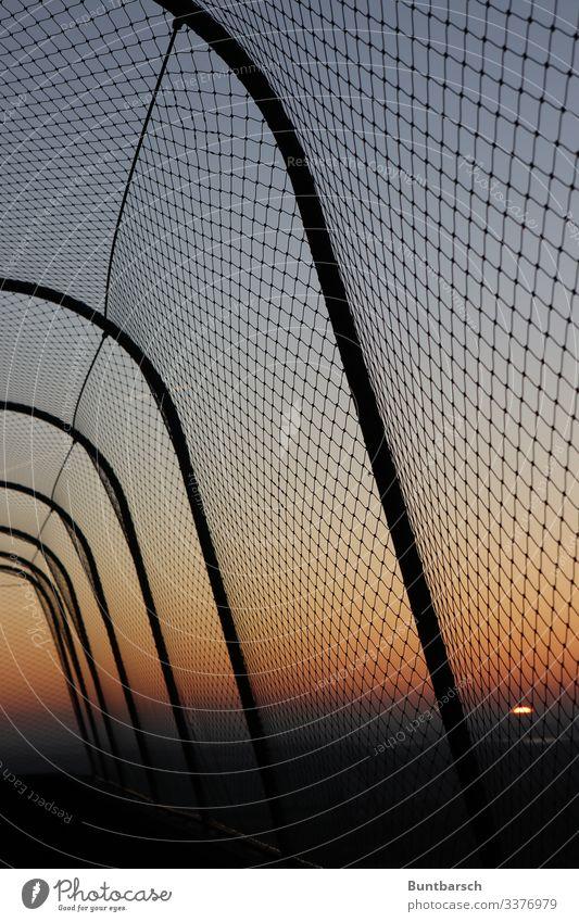 Schutzzaun im Abendlicht Zaun Grenze Maschendraht Maschendrahtzaun Abendrot Sonnenuntergang orange Metallzaun Sicherheit Barriere Menschenleer Außenaufnahme