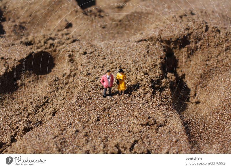 Zwei Modellfiguren- männlich und weiblich- im Sand am Strand Paar mann frau strand sand feststecken humor skuril klein modellfigur spielzeug urlaub sommer