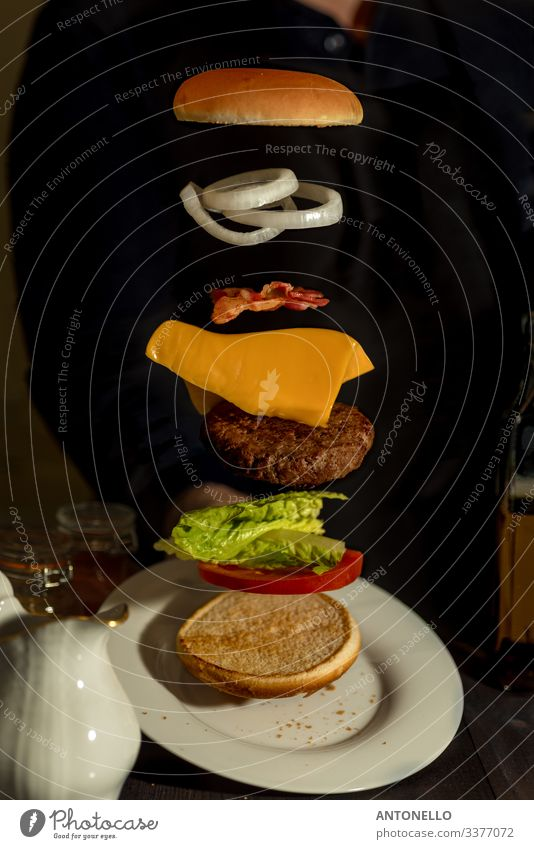 Sandwich mit fliegenden Zutaten auf weißem Teller angeboten Lebensmittel Fleisch Käse Salat Salatbeilage Tomate Zwiebel Ernährung Essen Mittagessen Büffet
